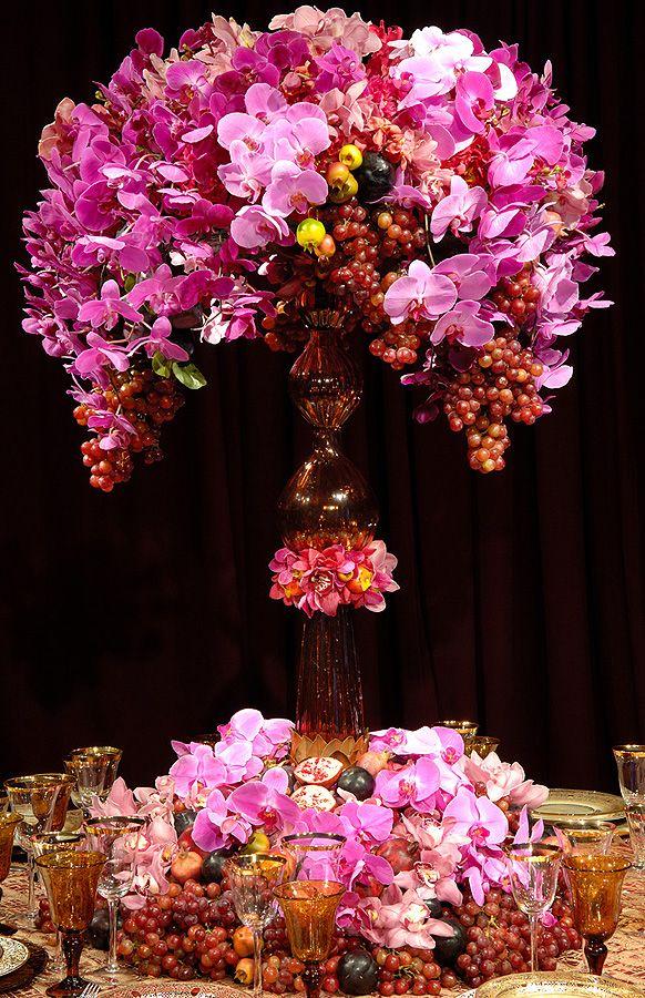 Arranjo de festa feito com orquídeas e frutas.