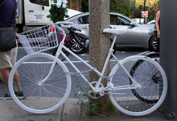 "Anita Kurmann's ""ghost bike"" is fastened to a street sign at the Back Bay intersection where she died, in this August file photo. (Hadley Green for WBUR)"
