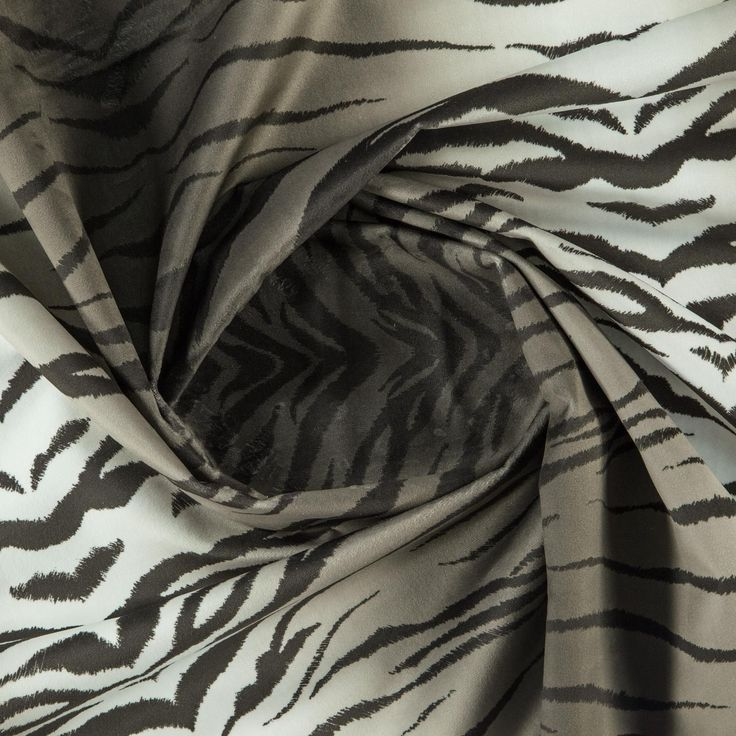 An animal skin printed furnishing fabric available in a multicoloured - grey - brown colourway. This article has a synthetic composition, and is suitable for curtains and upholstery.