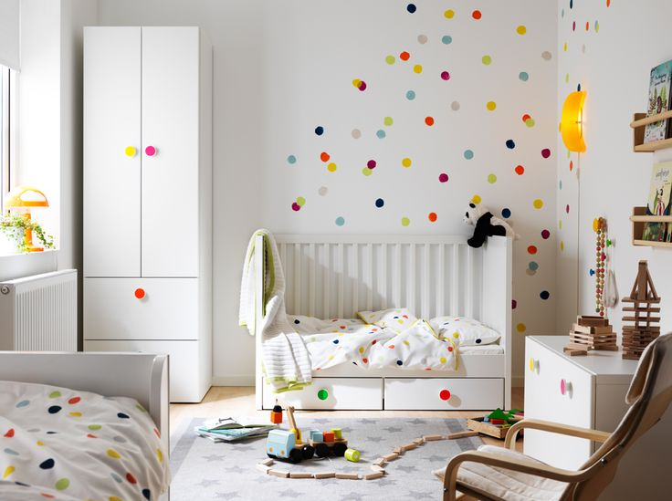 A small children's bedroom furnished with a white crib with floor drawers, converted into a children's bed. Shown together with a white wardrobe and a storage bench with colorful knobs.