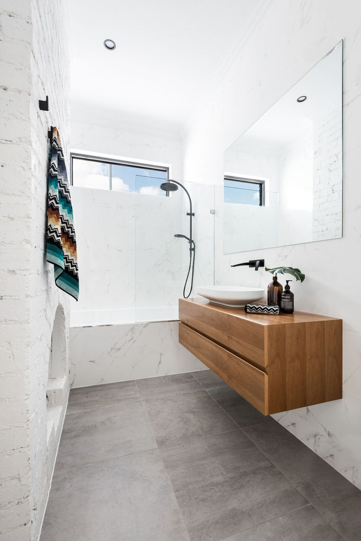 In this renovated bathroom, an original fireplace has been left as a design feature, while the rest of the bathroom has been updated with a large mirror and floating wood vanity.