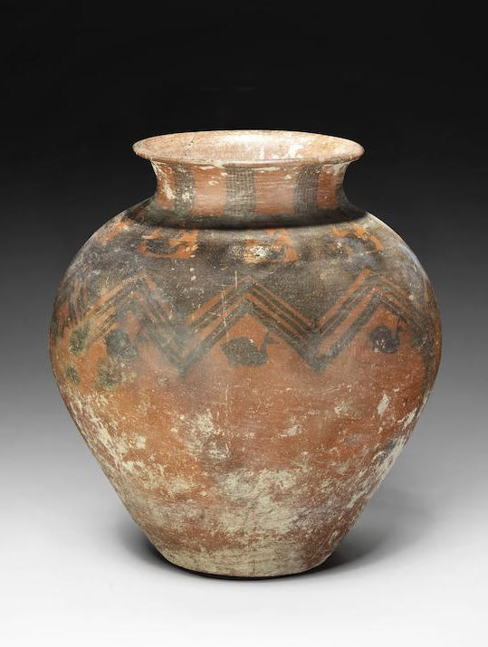 Anatolian pottery vase, 2nd millennium B.C. The rounded vase tapering to the base and neck, with a flaring mouth, the red burnished ground decorated with black painted decoration composed of birds and cross-hatching around the shoulder, bands of zigzag and further birds around the body, 68 cm high. Private collection