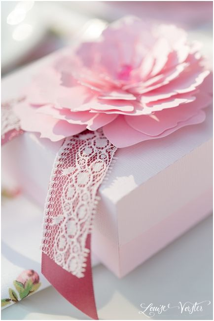 Close up of flower on invitation box, showing detail of the different shades of lace and ribbon.