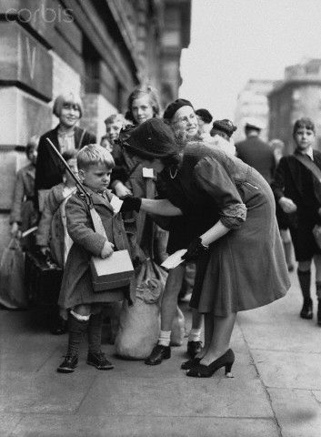 A women checks the identification label of a boy evacuee armed with a toy gun. September 1941, UK.