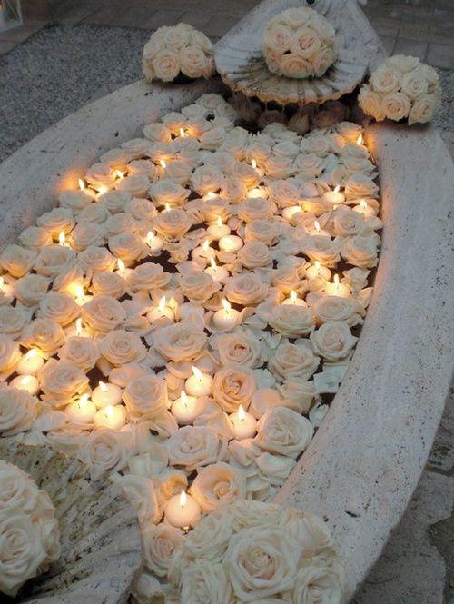 .Dans une vielle auge, fleurs et bougies chauffe-plat