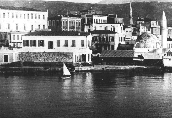 Χανιά το λιμάνι. Διακρίνεται μπροστά μας το τo Τζαμί του Κιουτσούκ Χασάν ή Γιαλί Τζαμισί, αριστερά το κτίριο του Τελωνείου, πιο πίσω το Τούρκικο σχολείο και στο βάθος ο μιναρές του Αράπ Τζαμί στη συνοικία Καστέλι που καταστράφηκε από τους βομβαρδισμού