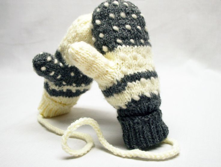 Children's winter grey and white thrummed mittens. Thrummed mittens are mittens that have pieces of wool roving knit into them with the roving ends to the inside and loose. Over time as the mittens ar