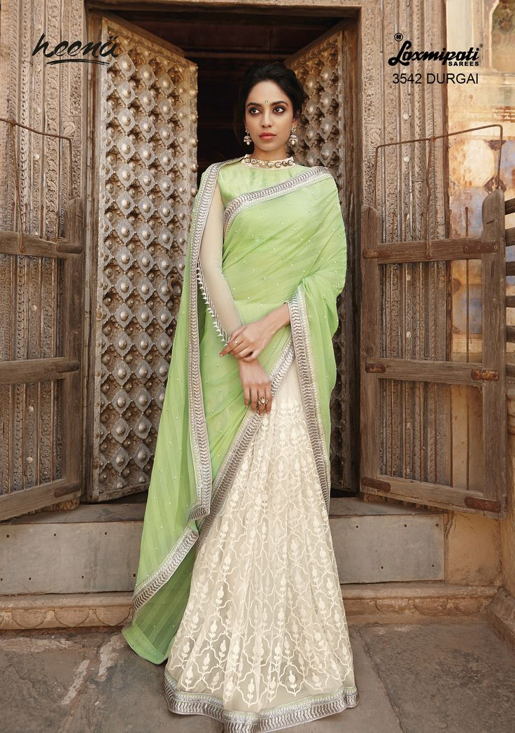Eye catching combination of Pista green and off white half and half chiffon cum net saree with purified resume Jari work on net carrying silk jacquard blouse.