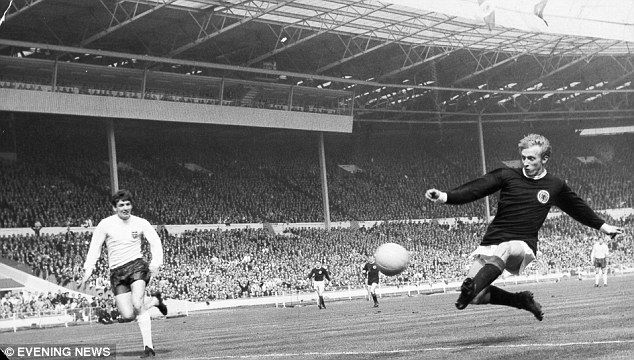 Manchester United great Denis Law (right) tries his luck at goal for Scotland at Wembley