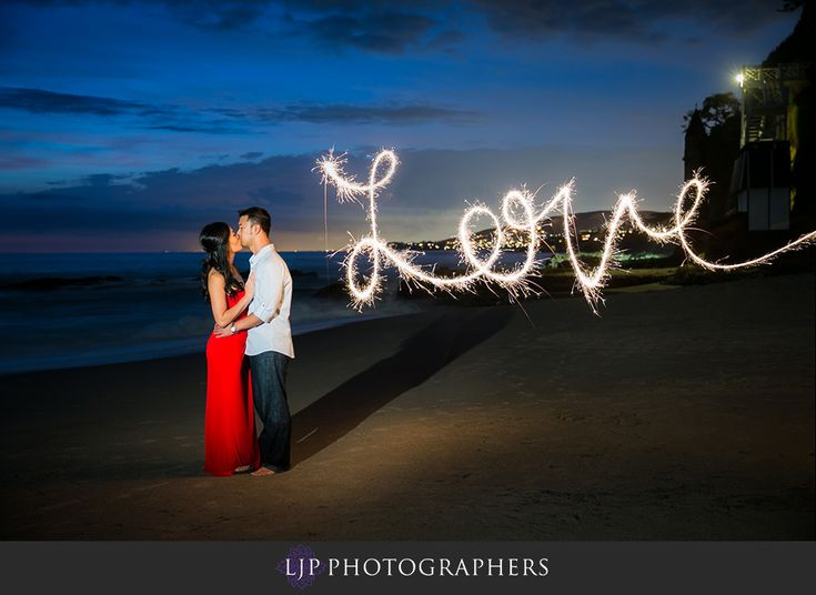 "Love everything about this photo - how the red dress adds a bright splash of color to the dark background, the pose, their long shadow in the sand, the color of the sky, the word ""love"" written in the sky. Definitely want to recreate this one"
