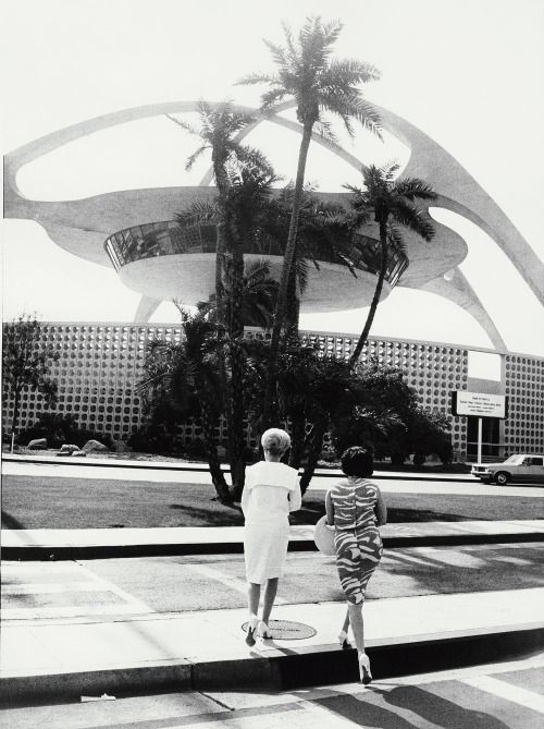 1964 With his trademark tilted horizon, Garry Winogrand's photograph of two women in front of the Theme Building by architects William Pereira, Paul R. Williams, Charles Luckman, & Welton Becket | Los Angeles International Airport (LAX) - Via