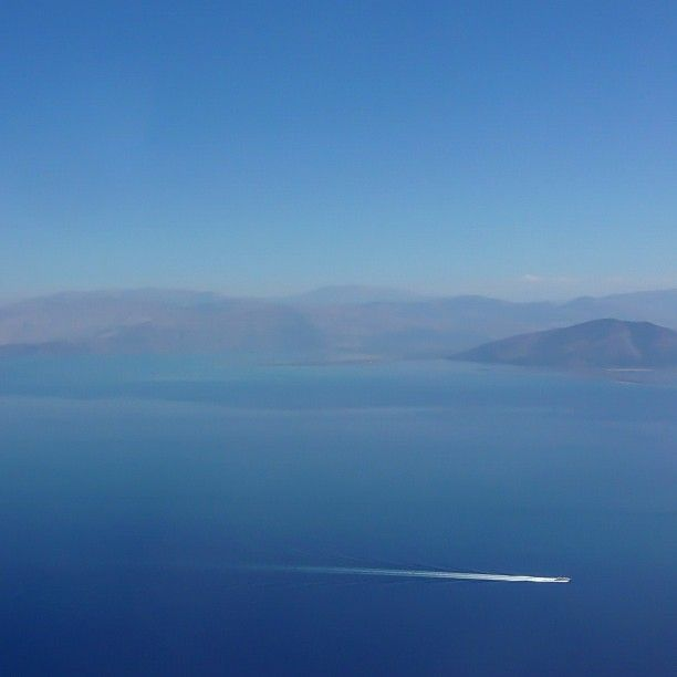 Blue sea, blue sky, a boat, mountains in the distance. Shot shortly before landing in Kerkyra, Corfu Greece. Photo from the Instacanvas gallery for dsm1972.