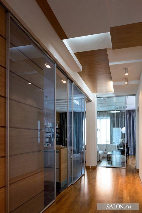 Вид из коридора на гостиную.  Раздвижные перегородки из стекла, Rimadesio. Чтобы спрятать вентиляцию и кондиционирование без потери высоты помещения, был сделан разноуровневый потолок, оформленный в едином стиле с общественной зоной
