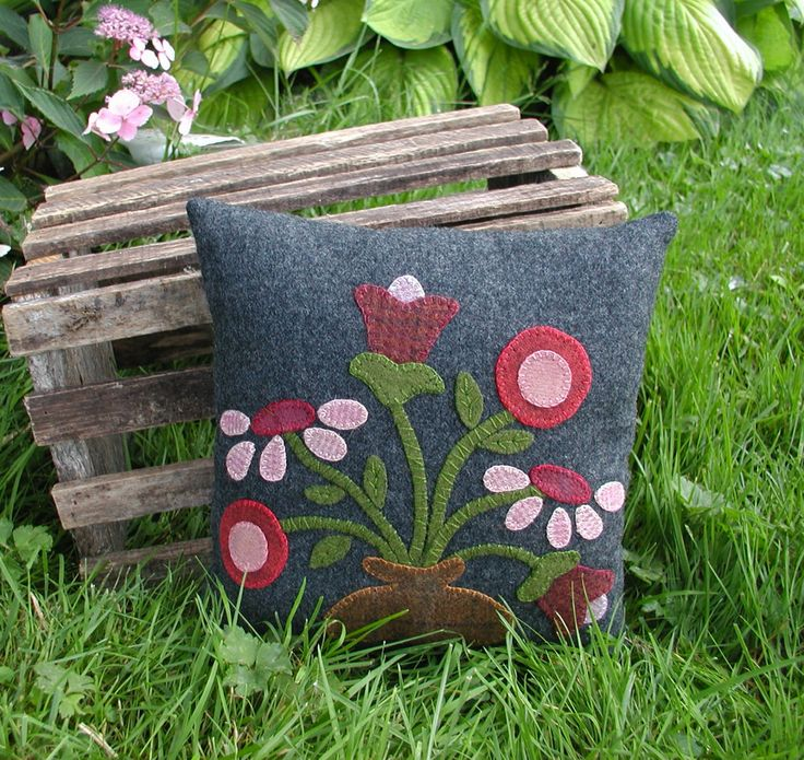 This primitive style pillow is made of 100% wool. The pattern features a bouquet of flowers in a rustic vase. Each detail of the flower, stem and leaves are made from 100% wool and hand-sewn with pearl cotton thread to a piece of gray wool, using a blanket stitch. I used the same gray wool for the backing. This piece would look cute on a chair or bench. You will receive the pillow only, all other items shown in photos are not included. The finished size is 9 x 9. Ready to ship. This item…