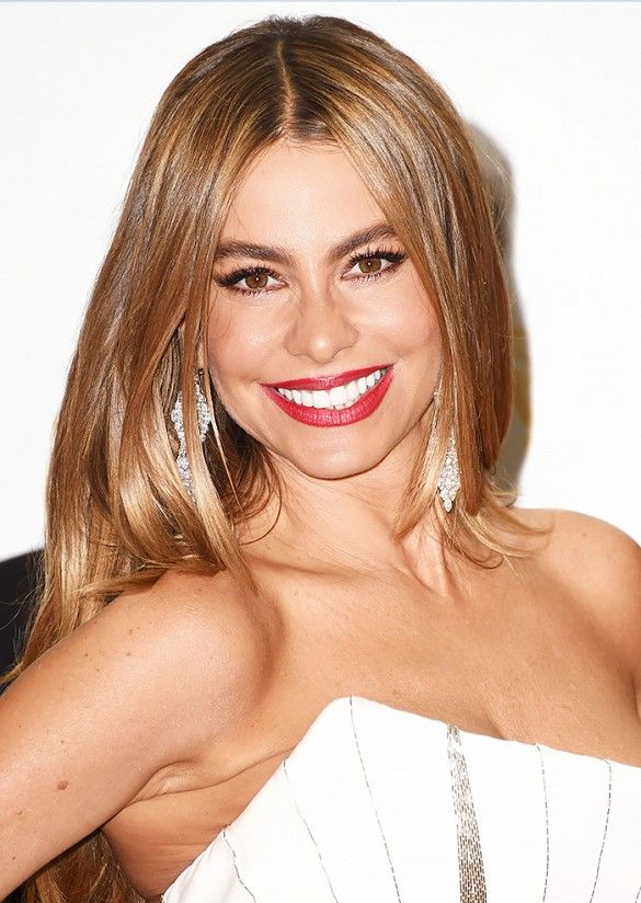 Sofia Vergara looks stunning as usual with caramel-colored blown out waves and red lips.