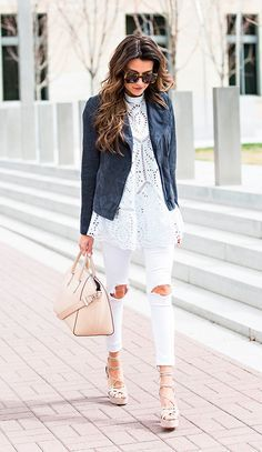 Christine Andrew caminha nas ruas usando camisa de renda branca, jaqueta de chamois azul marinho, calça skinny branca destroyed, sandália de amarrações nude, bolsa nude e óculos escuros