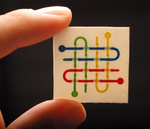 Braid in Fingers: This three-dimensional device has four channels that cross each other multiple times in a basket-weave pattern.  Aqueous dyes (food coloring in water) is wicked through the network of channels by capillary action. The device was made from two layers of patterned paper and one layer of double-sided tape, and it measures 3 cm x 3 cm.