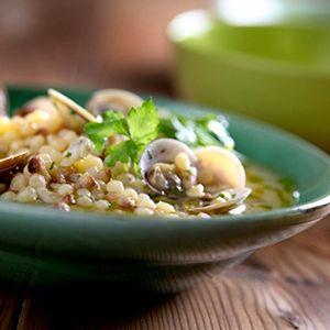 """Fregola con vongole - Een traditioneel Sardijns recept: fregola in bouillon – het is geen soep en het is geen """"gewoon"""" pastagerecht maar zit hier precies tussenin! Als je geen vongole kunt krijgen, kun je voor dit recept natuurlijk ook gewoon mosselen gebruiken."""
