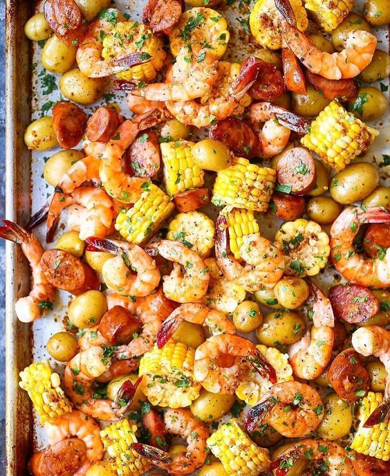 """SHEET PAN SHRIMP BOIL ~ 1 pound baby Dutch yellow potatoes 3 ears corn, each cut crosswise into 6 pieces 1/4 cup unsalted butter, melted 4 cloves garlic, minced 1 tablespoon Old Bay Seasoning 1 pound medium shrimp, peeled and deveined 1 (12.8-ounce) package smoked andouille sausage, thinly sliced 1 lemon, cut into wedges 2 tablespoons chopped fresh parsley leaves DIRECTIONS:  Preheat oven to 400 degrees F. Lightly oil a baking sheet or coat with nonstick spray. In a large pot of boiling…"