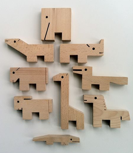 """ZOO (1969)    """"Ten delightfully whimsical animals, cut from solid wood blocks, invite many kinds of play. They stand alone, and may be lined up to form a circus parade 3 feet long. They may be stacked in many amusing ways, or may be built skyward, one balancing on the other (not easy to do). And they may be crayoned, painted or decorated, if desired. They are a versatile menagerie!"""""""