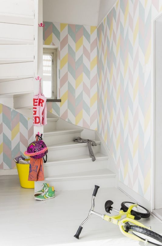 Kira Wallpaper - A radiant geometric wallpaper featuring large scale chevrons in duck egg, pink, yellow and white. A worn effect on the design adds subtle interest.