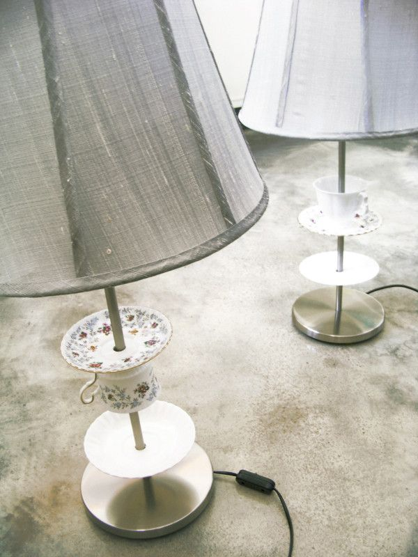 Old English mismatched china tea sets threaded onto contemporary stainless steel lamp bases with grey raw silk lamp shades.