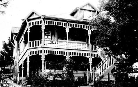The St Clair Guest House, Healesville. A two-storied large weatherboard house with wide verandas on both stories; there are some attic rooms. Wooden turned verandah posts; the house is freshly painted. The house is built into the side of a slope, and there is some washing hanging on the line in the back garden. Ferns and roses in the front garden, and steep wooden steps to the upper level. #HealesvilleHistory