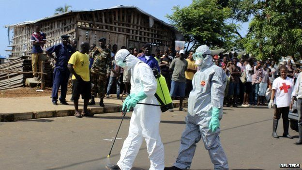 Health workers spray themselves with chlorine disinfectants after removing the body a woman who died of Ebola virus in the Aberdeen district of Freetown, Sierra Leone, on 14 October 2014.