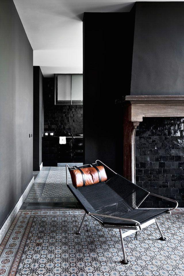 patterned tils black walls black armchair /