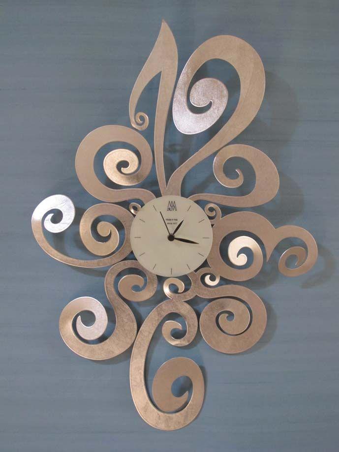 Reloj modelo NOEMI Plata Elegante y original reloj de pared. Se fabrica en color blanco o bronce o con los acabados en pan de oro o plata.
