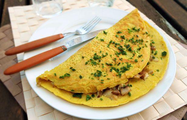 Omelette vegan aux champignons  Ingrédients : (pour une grande omelette)  Pour l'appareil :  - 150g de tofu soyeux - 10cl d'eau - 50g de farine de pois chiche - 15g de fécule - 1 pointe de couteau de curcuma (utilisé pour la couleur, il est facultatif) - sel, poivre  Pour la garniture : - 180g de champignons - 1 oignon - 1 gousse d'ail - un filet d'huile d'olive - Une petite poignée de persil et de ciboulette hâchés