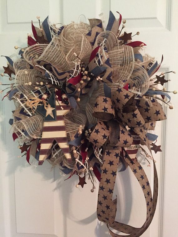 This primitive Americana patriotic wreath is made of ivory and cotton burlap deco mesh. I then accented with a burlap navy chevron ribbon and Americana canvas stripe ribbon throughout. I added a primitive American Wood Star and a primitive Americana wood Heart that says Stars and Stripes Forever. Then I added ivory pip berries -most are accented with rusty stars. I then tied it all together with a canvas ribbon accented with navy blue stars. This striking primitive Americana wreath measures…