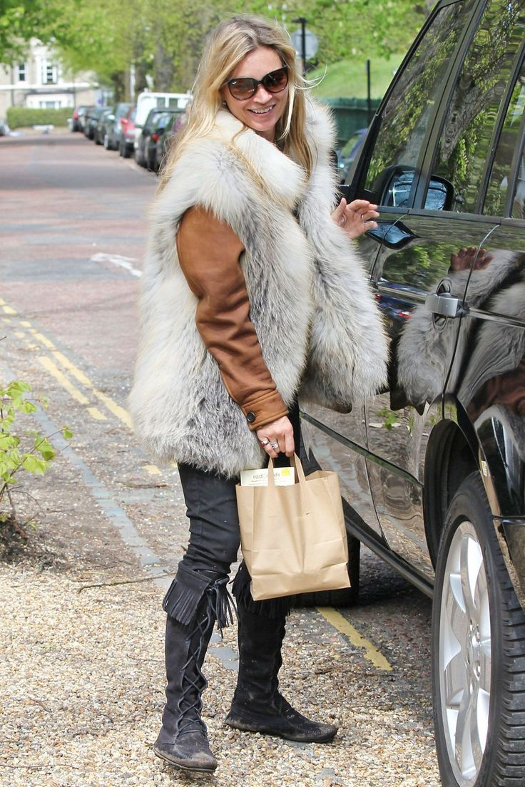 Out in London wearing a fur gilet, tan leather jacket and knee-high flat boots.