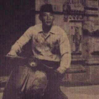 Mr. Soekarno driving a vespa motorcycle