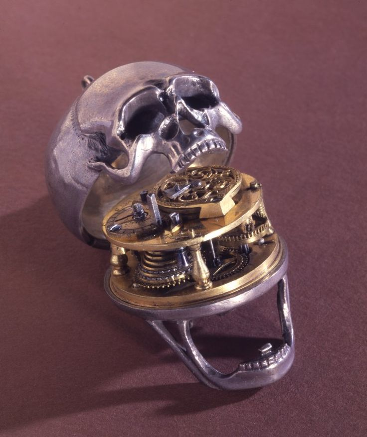 SILVER CASED VERGE WATCH IN THE FORM OF A HUMAN SKULL [MOVEMENT AND DIAL NOT ORIGINAL]. . MOVEMENT Circular gilt-brass plates with four baluster pillars. One pillar is a modern replacement, two original pillars are now retained in the front plate by blued-steel screws. Ratchet and click set-up mounted on the dial side of the pillar-plate. Fusee with chain and standard stop-work.