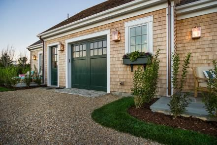 A carriage door opens up to a simple but functional one car garage with plenty of room for pet items and beach supplies.