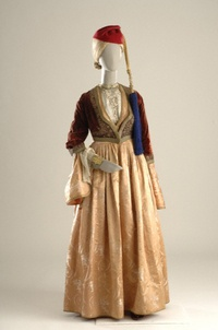 """This costume was the urban dress of the Athenian woman, known as the """"Amalia costume"""" after the first queen of Greece who established it as the formal attire of the Royal Court. This style spread throughout Greece in one variation or another according to societal or personal tastes, and influenced nearly all urban women's costumes. The long gown, known as the kavadi, was made of a luxurious imported fabric, usually brocade, with an open bodice to display the elaborately embroidered bib of…"""