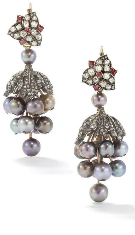 An antique pair of natural coloured pearl, diamond and ruby ear pendants. The diamond and ruby floral surmount suspending a stylised bunch of variously coloured iridescent grey and black pearl grapes, 5.3-6.5 mm, to a realistically modelled diamond-set cap, length 5 cm. Via Phillips.