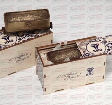 Корпоративный подарок из шоколада: шоколадная фигура «Вагонетка с логотипом компании», габариты 110х45х50мм, вес 160-170 гр.  Бельгийский шоколад Barry Callebaut, темный  54%.  Шоколад относится к классу «премиум», настоящий темный шоколад высочайшего качества. Упаковка: подарочный пенал из фанеры с полноцветной печатью по поверхности (брендирование).  Размер упаковки: 140х65х80мм. Декоративный наполнитель – стружка из пищевого пергамента.  Сроки производства: 1-1,5 месяца, если проект…