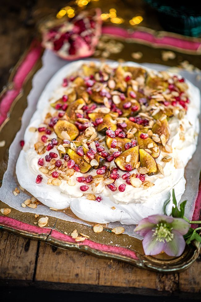 Rosewater pavlova, topped with ricotta whipped cream, syrup-soaked figs and pomegranate seeds – a spectacular yet easy Christmas dessert
