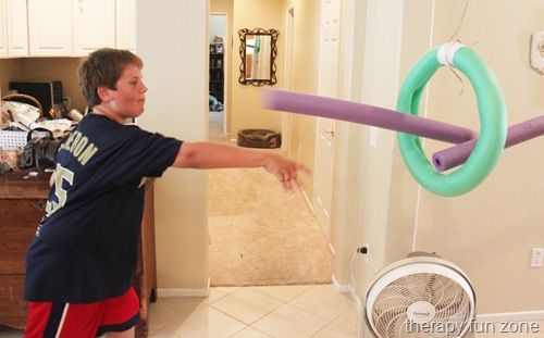Throwing pool noodle successfully through the loop. Can be graded up or down by increasing or decreasing the distance away from the loop.