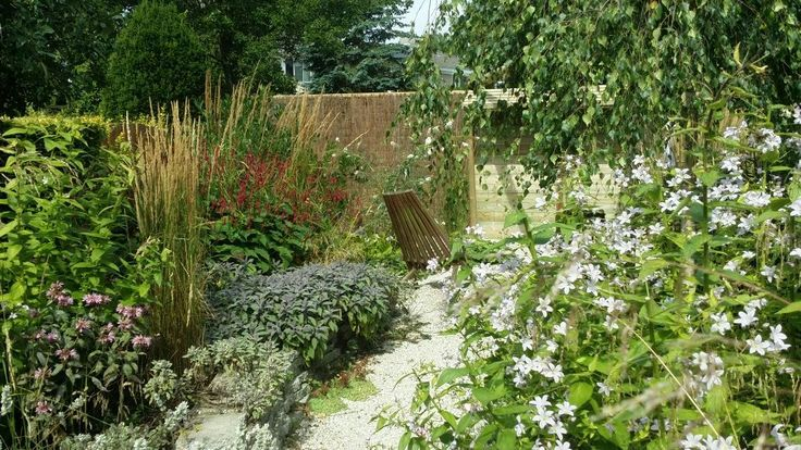 Natuurlijke tuin met stapelmuurtjes van hergebruikte tegels, aangelegd door Hoveniersbedrijf Neeleman.