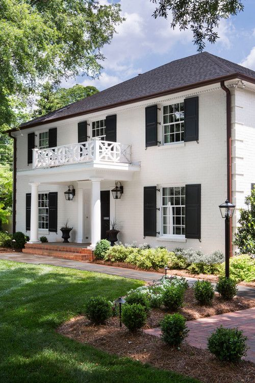 Beautiful Colonial-style white home with columns under the front balcony and classic black shutters.