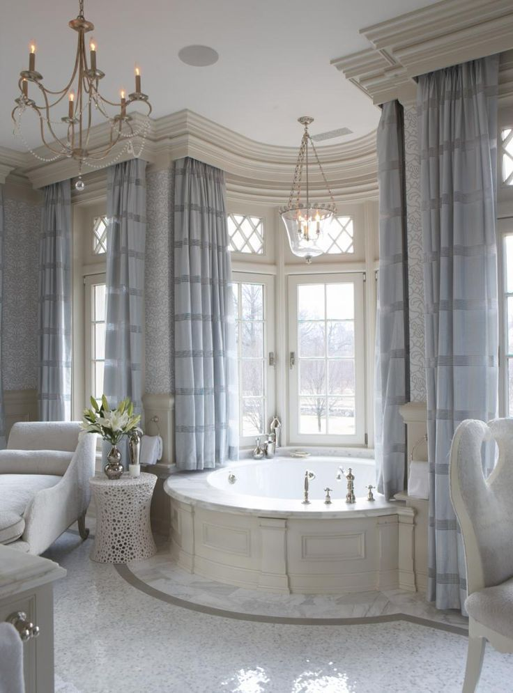 Very elegant bathroom design. The circular bathtub is the focal point of the room surronded my large windows. The drappery and fabric chaise lounge give the room a very soft romantic feeling.