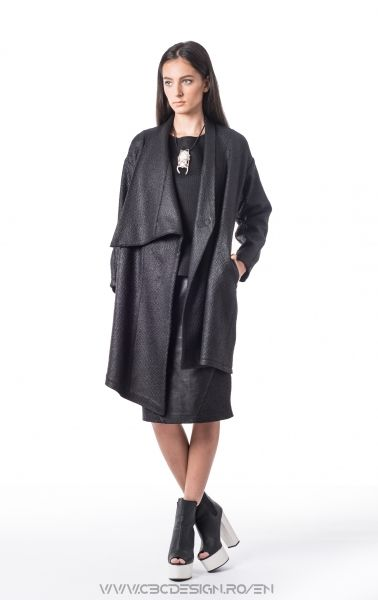 Asymmetric overcoat from a coated fabric with gravel-like texture. It closes with two hidden sew-on snap fasteners, has side pockets and high collar. Its interior is animated by grey bands that border the edges all-around. Having a loose fit and slightly feminine silhouette, it can be easily worn in an elegant outfit, fastened at both snaps; a grungy feel is given when worm with leather pants, boots and fastened with one snap; for a chic vibe, wear it on the shoulders for a smart layering.