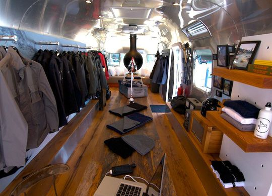 aether apparel in aetherstream vintage airstream full of green features including solar panels, reclaimed wood floors, modular shelving