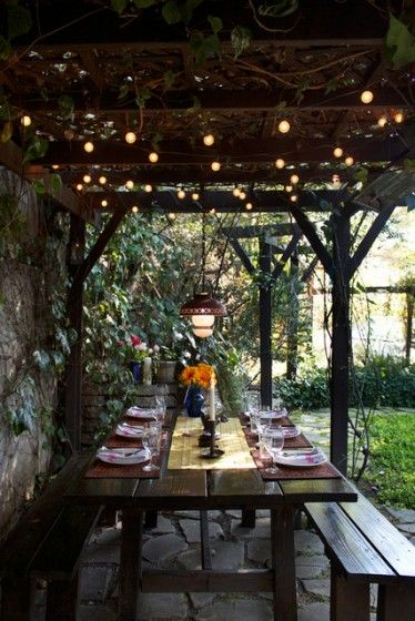 A picnic table sets the scene for a rustic garden dinner party beneath a vine-strewn arbor. Overhead, string lights twinkle among the foliage. Get ideas for creating enchanting outdoor spaces at http://www.lender411.com/featured-article-create-an-outdoor-haven-to-enjoy-the-summer/