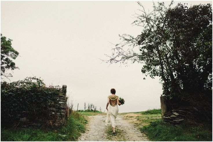 Wedding Photography at Fforest | The bride walking to be married. I love the back of the dress shot. It wasn't the nicest of day weather wise and the mood of this frame is everything to me.   Alternative and stylish | Reportage