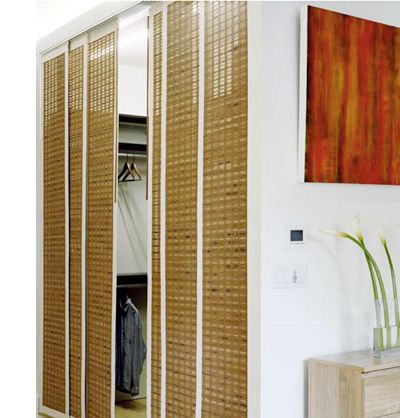 If you live in a small space, replace traditional closet doors that swing out with curtains or hanging screens. Image: Woven Wood Panels from the Shade Store.  Via Apartment Therapy:  20 Ways to Organize Your Bedroom Closet