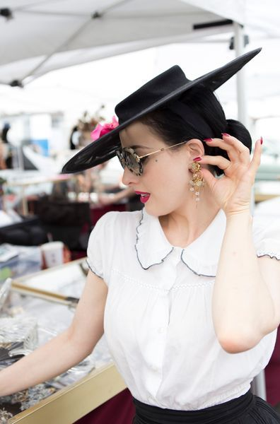 Dita Von Teese, with interior decorator Stacia Dunnam, shopping at the Santa Monica Airport Outdoor Antique and Collectible Market. Dita is wearing a vintage 1950s black skirt and hat, Marc Jacobs flats, a Fifi Chacnil bodysuit, Miu Miu vintage sunglasses and MAC lipstick in Good Kisser, and is carrying a 1950s lucite purse with a vintage polka dot scarf. October 28, 2015. Photo: Sera Lindsey.